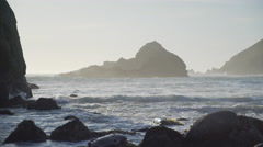 Waves lap on Pfeiffer beach with view of dramatic rocks Stock Footage