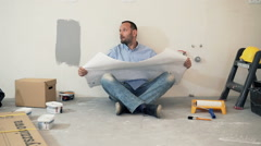 Young man reading blueprints while sitting on floor at his new home Stock Footage