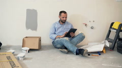 Young man with tablet and blueprints sitting on floor at his new home - stock footage