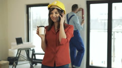 Young woman talking on cellphone at her new home, male worker in the background Stock Footage