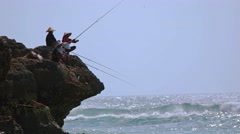 Balinese fishermen angling from the beach rocks, with sound. - stock footage