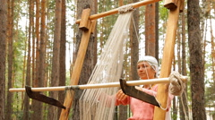Two women weaving cloth using a traditional ancient machine Stock Footage