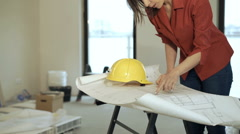 Young woman working with blueprints at her new home - stock footage