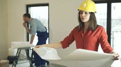 Young woman reading blueprints at her new home, male worker in the background Stock Footage