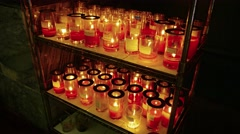 Votive candles burn on a tiered rack inside a temple in Macau. Stock Footage