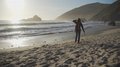 Tourist walks along Pfeiffer beach Stock Footage