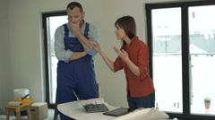 Woman with tablet and blueprints giving reprimand to male worker at her new home Stock Footage
