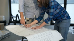 Woman and male worker reading blueprints and shaking hands at new home - stock footage