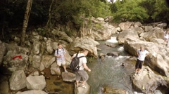 Tourists step precariously over rocks at Ba Ho Waterfall in Vietnam. Stock Footage