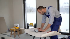 Male worker working with laptop and blueprints at new home - stock footage