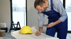 Male worker working with smartphone and blueprints at new home - stock footage