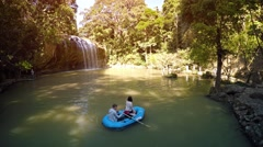 Tourists in rubber raft, drifting in natural pool at base of Prenn waterfall Stock Footage