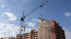 Builder works at against background of the construction site high-rise buildings Stock Footage
