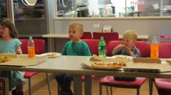 Outside looking in children eating pizza at a restaurant. Stock Footage