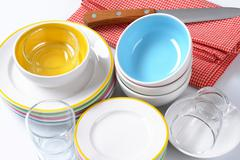 Dinner set consisting of deep bowls, dinner plates, side plates and glasses Stock Photos