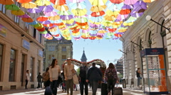 Happy tourists at one street decorated with colored umbrellas Stock Footage