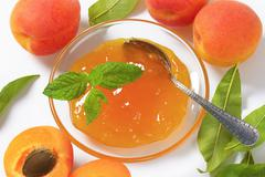 Jam on glass plate and fresh apricots - stock photo