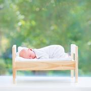 Tiny newborn baby sleeping in a toy bed next to a big window into a garden Stock Photos