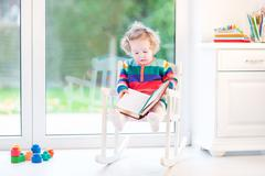 Cute funny toddler girl reading in a white rocking chair at a big window - stock photo