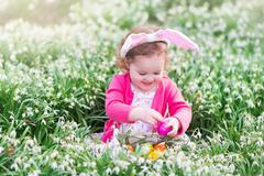 Little girl with bunny ears on Easter egg hunt - stock photo