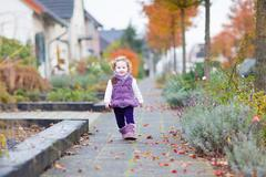 Adorable toddler girl walking down a beautiful road in a little village - stock photo
