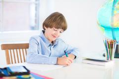 Happy smiling school boy, smart student, doing homework cutting - stock photo
