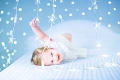 Little toddler girl playing in a white bed between sparkling blue lights Stock Photos