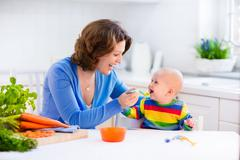 Mother feeding baby first solid food Stock Photos