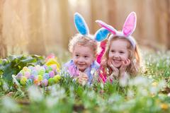 Kids on Easter egg hunt in blooming spring garden Stock Photos