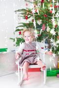 Happy laughing toddler girl with Christmas lights sitting in rocking chair - stock photo