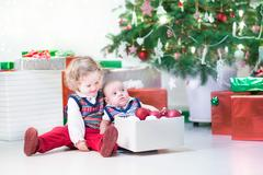 Little toddler girl and her newborn brother helping to decorate Christmas tree Stock Photos