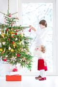 Adorable toddler girl helping her brother to decorate Christmas tree - stock photo