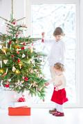 Beautiful toddler girl helping her brother to decorate a Christmas tree - stock photo