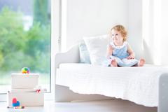 Cute toddler girl wearing a blue dress sitting on a bed reading a book - stock photo