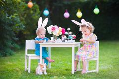 Kids playing Easter tea party with toys - stock photo