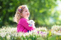 Little girl playing with bunny on Easter egg hunt - stock photo