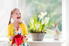 Little girl watering Easter flowers - stock photo