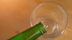 Beer pouring from a green bottle, top view Stock Footage