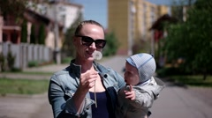 Young Woman With Her Baby Son Blows Dandelion Stock Footage