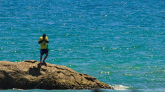 Guy Jumps from Rock into Azure Sea - stock footage