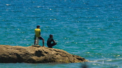 Backside Two Guys Stand on Rock against Azure Sea Stock Footage