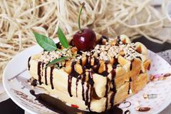 Belgian waffles with peanut chocolate sauce and cherries on a plate - stock photo