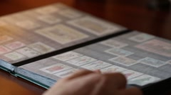 Collector considers stamps in an album through a magnifying glass - stock footage