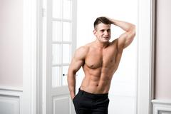 Shirtless sexy male model standing in the doorway home interior, looking away - stock photo