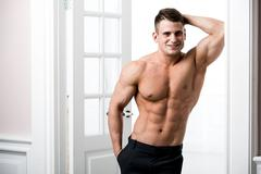 Portrait of a well built shirtless muscular male model against light background - stock photo