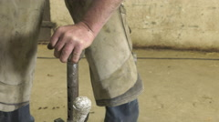 A craftsman farrier replace horseshoes Stock Footage