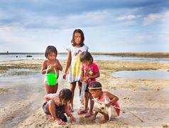 BALI, INDONESIA - AUG 20: Children playing on the waterfront, during low tide - stock photo