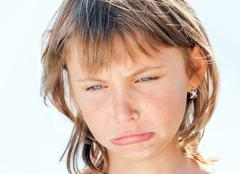 Offended face of young beautiful girl close-up on the background Stock Photos