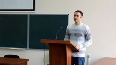 The young white ambitious student goes to the podium for the report - stock footage