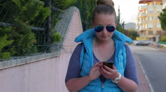 Active young woman writes a message using smart phone walking down the street  Stock Footage
